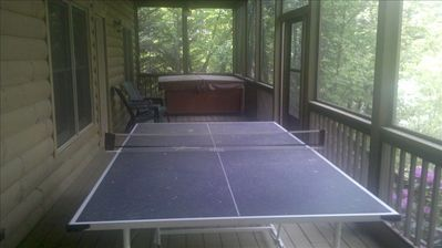 Lower screened deck with outdoor ping pong table and hot tub. Two fans overhead