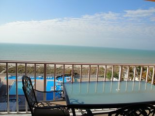 Indian Rocks Beach condo photo - View from living room over balcony patio furniture to beaches