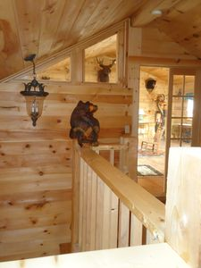 Top of stairs with the Great Room in background, as hand carved Bear keeps watch