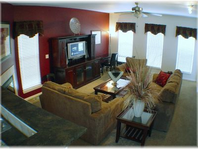 Large open LR with LCD TV, microfiber furniture, fireplace, and desk