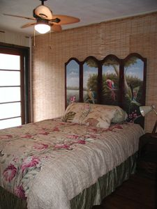 Bedroom 2 has a queen sized bed, hand painted headboard and tropical decor