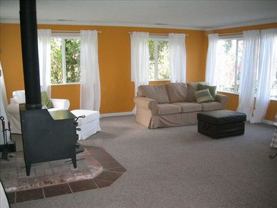 spacious living room with wood stove and lots of windows.