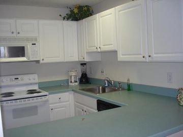 Kitchen with range, dishwasher, disposal, utensils, dishes, glasses & silverware