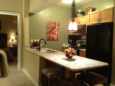 Fully stocked kitchen with gas stove, stainless/black appliances, granite.