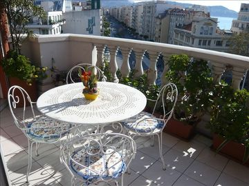 Large flowered terrace with table and chairs, overlooking sea, hills, town...