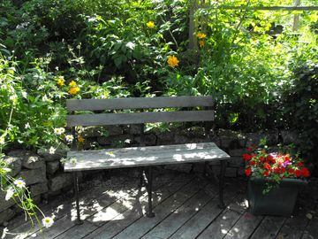 In summer our terraced decks are accented by rustic benches and vibrant flowers.