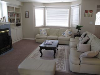 Bright living room with leather sofa set, gas fireplace and a bay window - Montgomery Estates house vacation rental photo