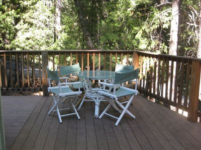 Deck has two sets of tables and chairs and a gas BBQ grill