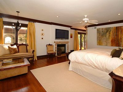 "Master bedroom with Cal King bed, 50"" plasma tv, and antique settee."