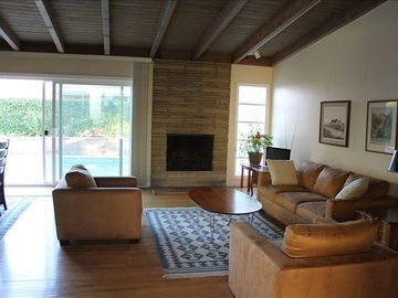 Living Room with fireplace -- sliding doors open to backyard pool area.