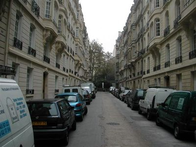 Elegant Haussmann building on left, quiet dead end street, private school at end