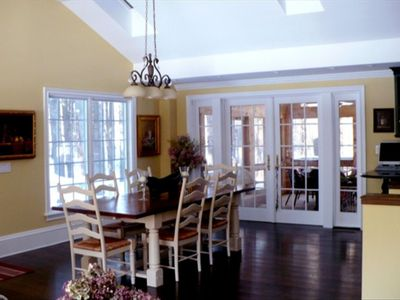 Open plan dining room with French doors to screened in porch