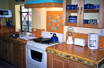 The kitchen has a gas stove, oven and large refrigerator