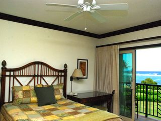 Waipouli condo photo - Queen bed with desk, TV, and reading area, full ocean views.