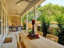 Large Patio featuring Outdoor Kitchen, Dining Table, multiple ceiling fans, TV.