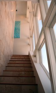 Looking up from steps. Window wall. Coral wall, teak floors, beautiful art