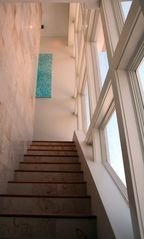 Inlet Beach house photo - Looking up from steps. Window wall. Coral wall, teak floors, beautiful art