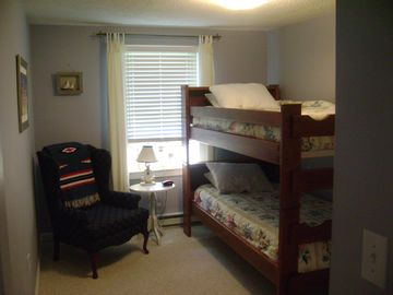 Cozy bedroom with bunk beds. Safety rail on top bunk