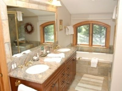 The master bathroom features granite countertops, double sinks, walk-in shower, a large bathtub, and a walk-in closet...which provides ample space for your winter wardrobe.
