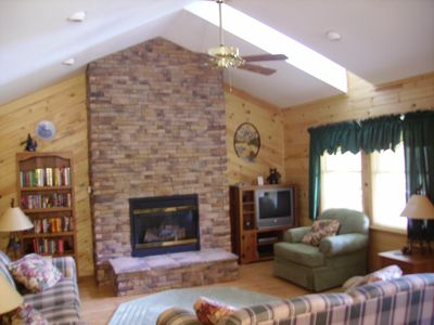 The living room features skylights, vaulted ceiling, and massive fireplace.