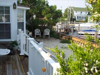 Stone Harbor property rental photo - 50' Wide Water Front - Upper Dine Deck - Shady Landscaped Area