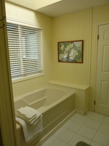 Upstairs master bath with full-size tub, shower, toilet, and two separate sinks