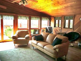 Delightful sun room with leather furniture, large tv, and a stocked game closet.