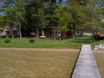 View of sandy beach, dock, fire pit, and clear lake. Cottage now green.