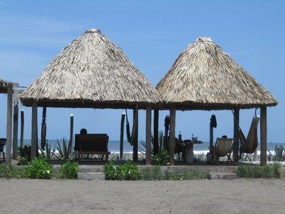 Palm thatched pangas in front of the beach