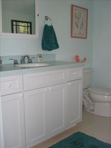Water-hued guest bath has ample towel rods. A 3rd bath w/ shower is on 1st floor
