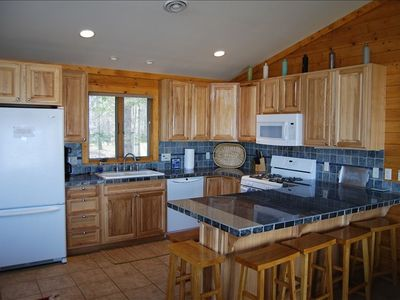 Custome countertops, walnut cabinets, tile floors and a large breakfast bar.