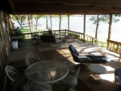 Outdoor covered deck with dining table and 2 relaxing areas30 feet from water