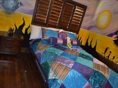 The second bedroom boasts a comfy queen bed, 40 inchTV and hand painted mural