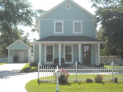 Cottage has awhite picket fence & detached single carport in the back.