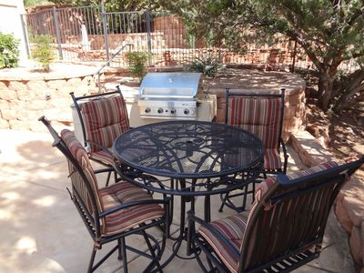 Modern gas grill with lots of outdoor seating for everyone.