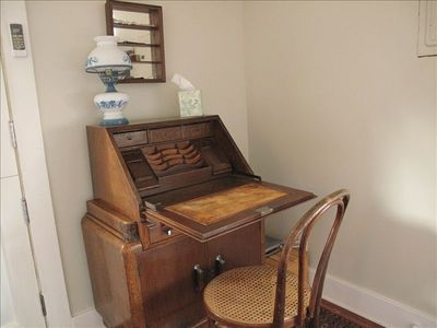 There are 2 desks. This antique secretary in the living area and an office desk.