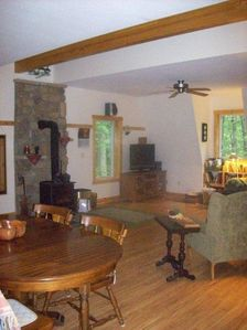 "Great room has Kitchen, Dining, TV viewing, Queen ""wall bed"", and warm stove."