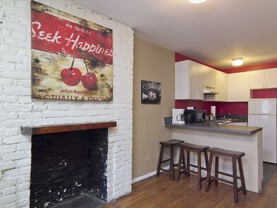 Exposed Brick Walls with white fresh paint, kitchen has bar stools.