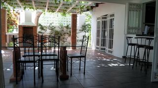 Playa Palmar house photo - Pergola, with barbecue, kitchen on right with bar, dining area foreground