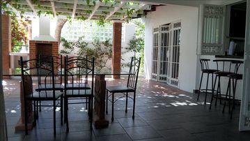 Pergola, with barbecue, kitchen on right with bar, dining area foreground