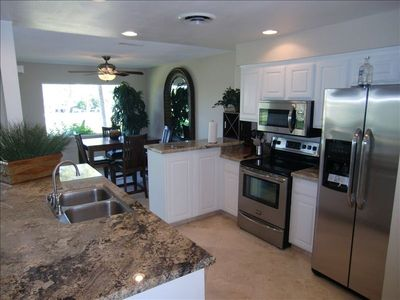 modern kitchen has granite counters, stainless appliances, travertine floors
