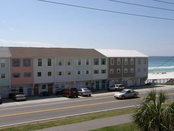Far Left, View of Sanddollar flamingo-colored townhome on white sand beach
