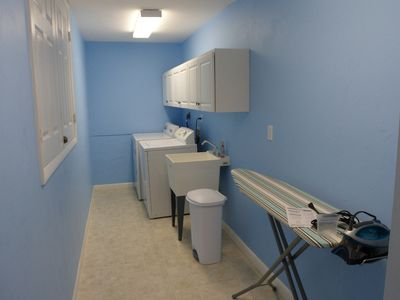 The large laundry room has full size washer and dryer, storage, and ironing!