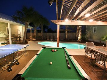 Night shot of backyard with landscape, arbor, and pool lighting