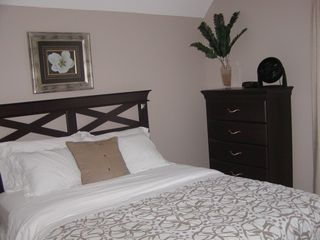 Grand Haven house photo - One of two main level bedrooms each with queen bed and vanity sink.