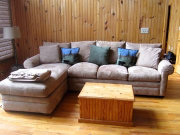 View of one of two large couches in living room that invite group gatherings.