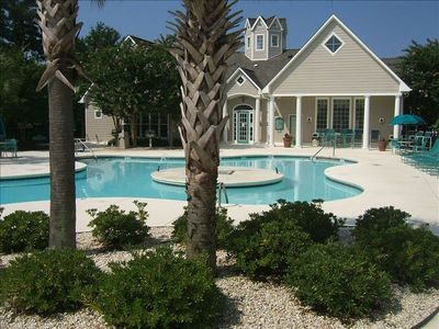 Beautiful pool w/ gas grills, abundance of tables, chairs and lounges.