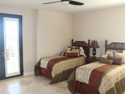 2nd floor bedroom features twin beds, private balcony & full bath w/dual vanity