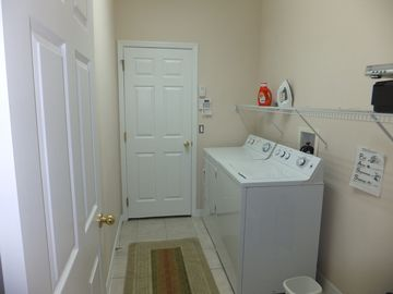 Laundry room with washer and dryer, ironing board and iron