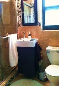 This bathroom is located next to the room with twin beds.